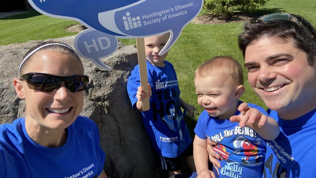 Shana Verstegen with her husband and two children, all dressed in blue, holding blue signs related to fighting Huntingtons disease