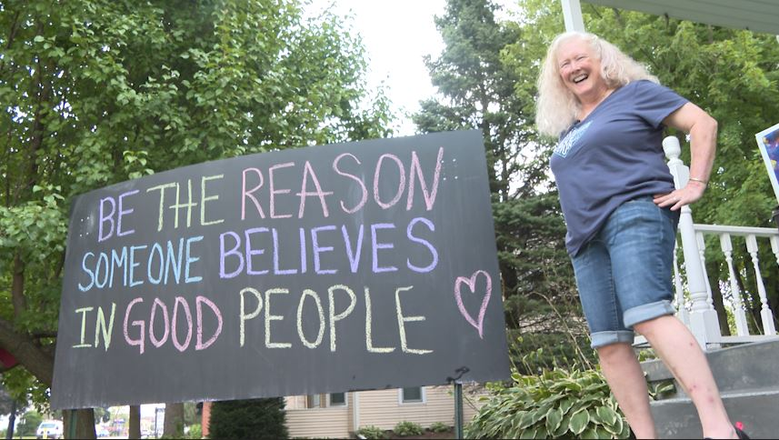 Deb Nies standing next to her chalkboard with a positive message