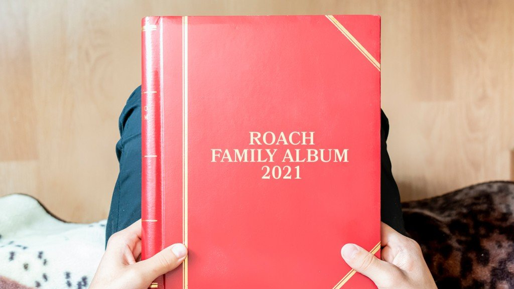 person holding a red photo album says Roach Family Album 2021