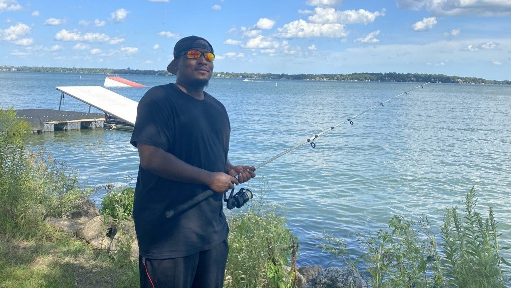 Brandon Wilkerson, 32, stands before Lake Monona, where he holds fond memories of fishing with his grandmother close to his heart.