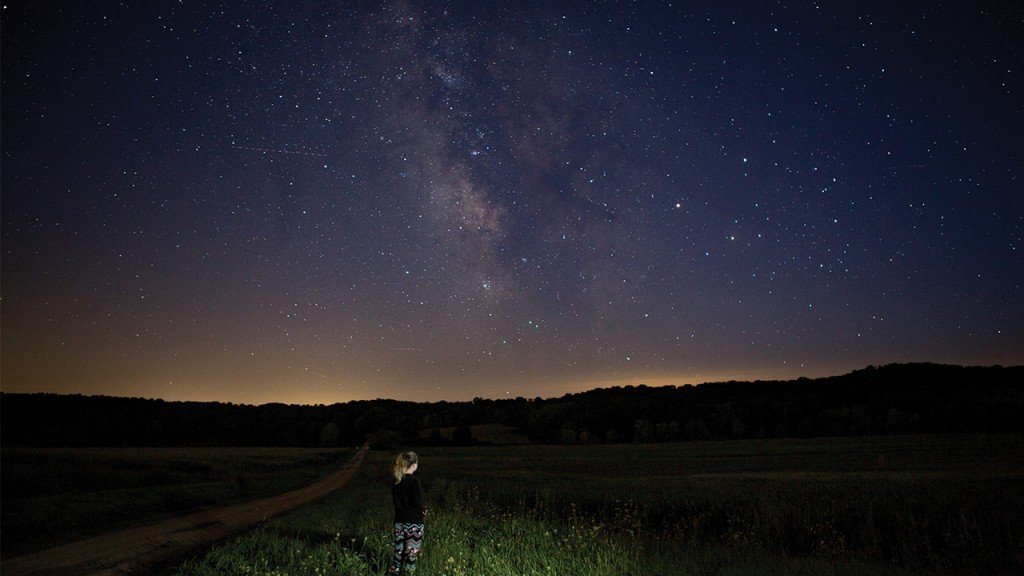 little girl standing in the middle of a field and looking at stars in a field at Donald County Park