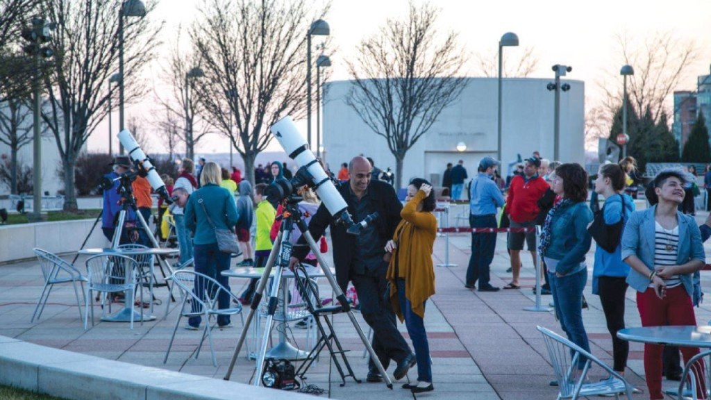 people gathered with telescopes at Moon Over Monona Terrace
