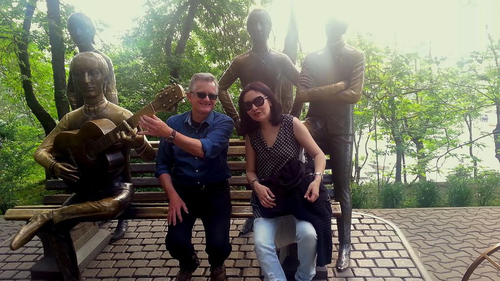 """Musicians Timothy Walsh and Akmaral """"Mergen"""" Zykayeva sit on a bench in Kazakhstan next to a sculpture of someone playing a guitar, with two additional standing sculpture people behind them.."""