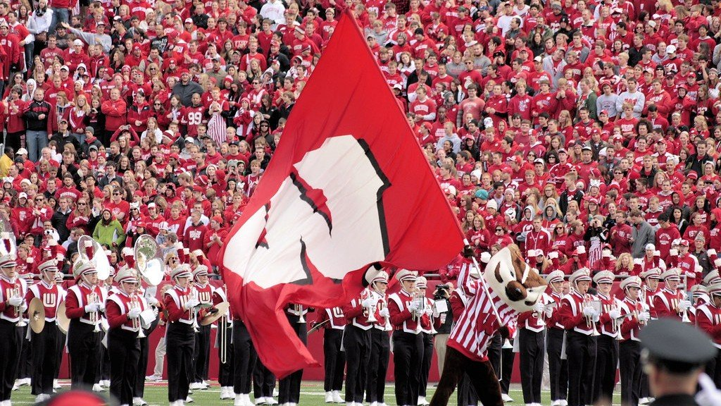 Bucky holds the Wisconsin flag at Camp Randall Stadium in front of the marching band and crowd.