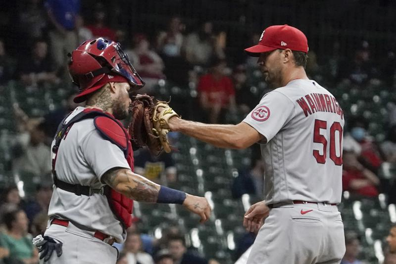 St. Louis Cardinals starting pitcher Adam Wainwright is congratulated by catcher Yadier Molina as he leaves the game during the seventh inning of a baseball game against the Milwaukee Brewers Friday, Sept. 3, 2021, in Milwaukee. The game marks the 300th game that Wainwright and Molina played in together. (AP Photo/Morry Gash)