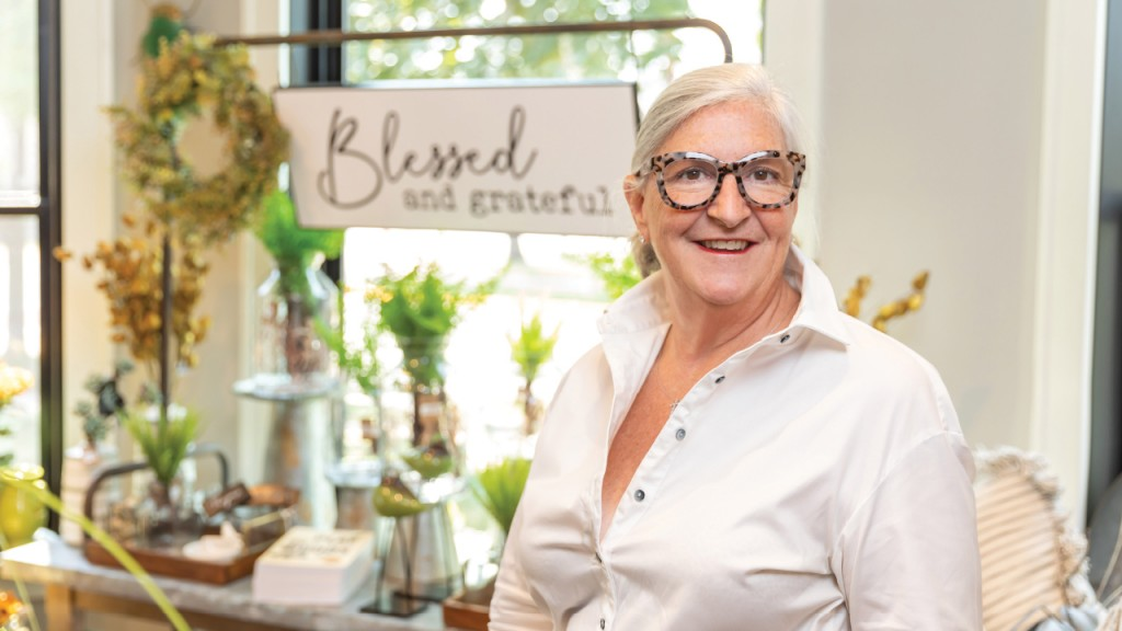 Lynn Mcfee standing in her shop in front of a sign that says Blessed and Grateful