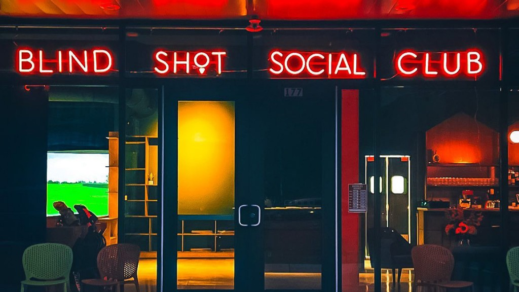 In this image Blind Shot Golf and Social Club's storefront is lit up at night. With the stores name hung up in neon letters.