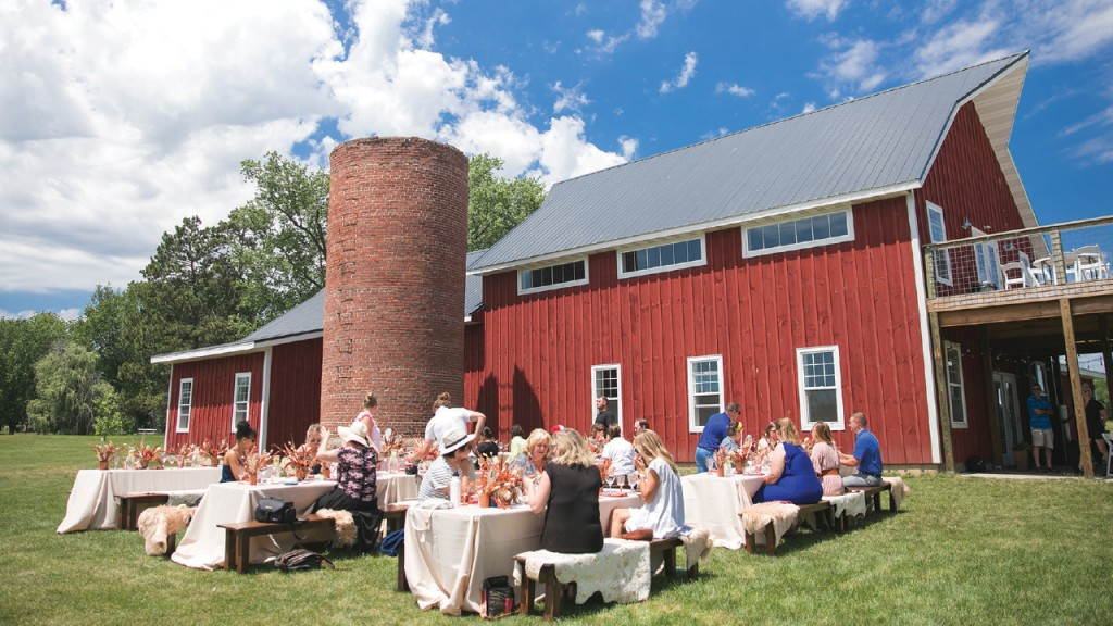 barn with tables and people gathered in front of the tables