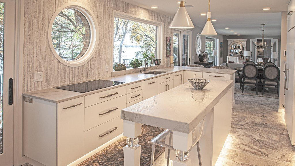 Modern white interior of galley kitchen with island and stool
