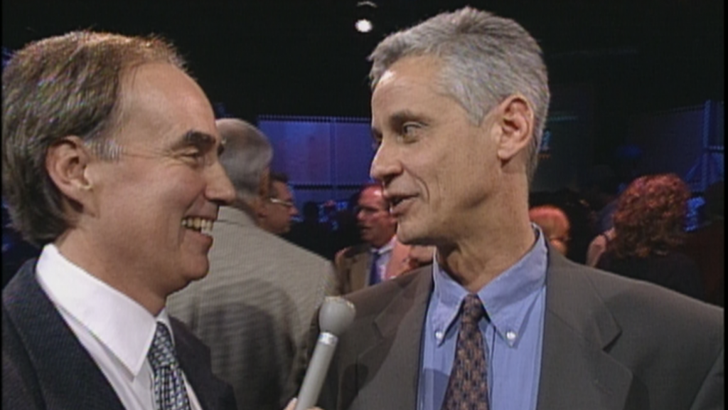 On the left Dave Iverson holds a microphone and interviews Andy Moore who is on the right