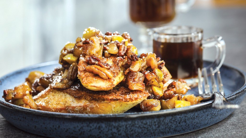 plate of french toast with fruit and pecans with a large container of syrup from Everyday Kitchen
