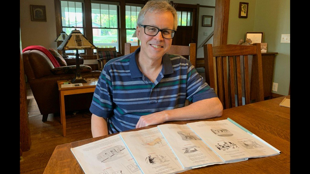 Paul Nesja poses in glasses and a short sleeved striped shirt at his dining room table with four copies of The New Yorker open before him that show his captions.