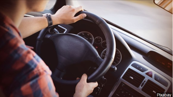 Individual driving and holding the steering wheel with both hands