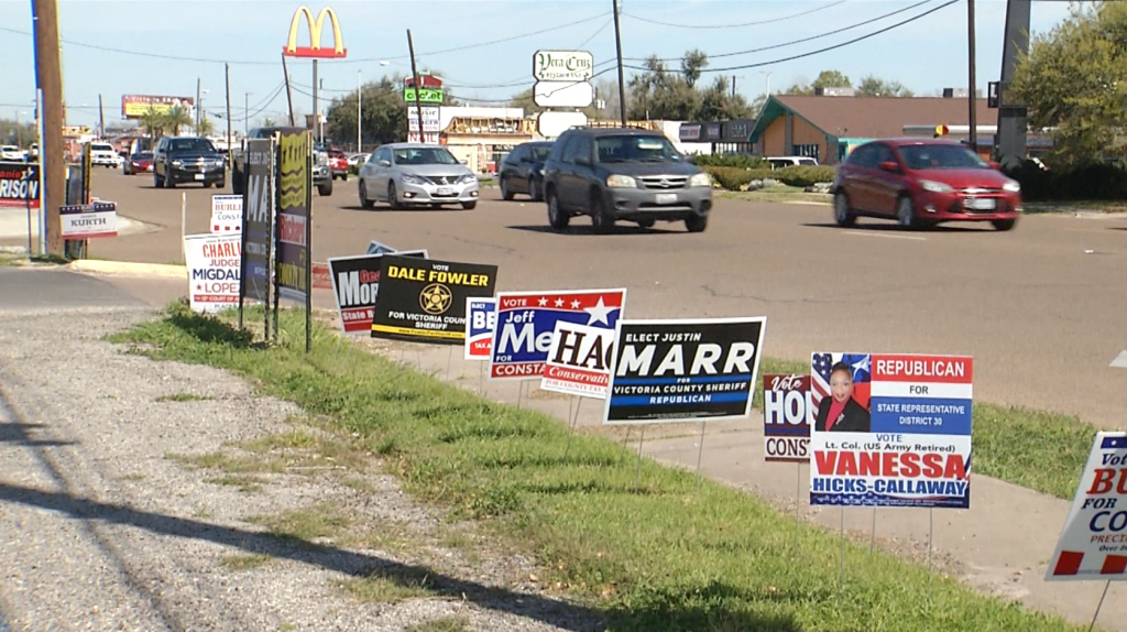 political campaign signs along busy road