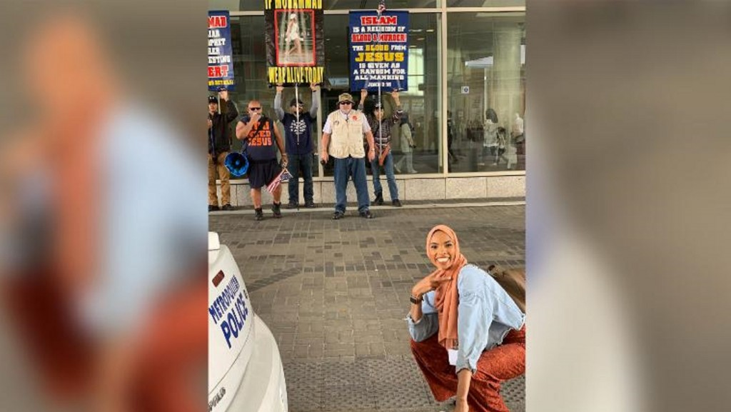 Hijab-wearing woman takes smiling stand against anti-Muslim protesters