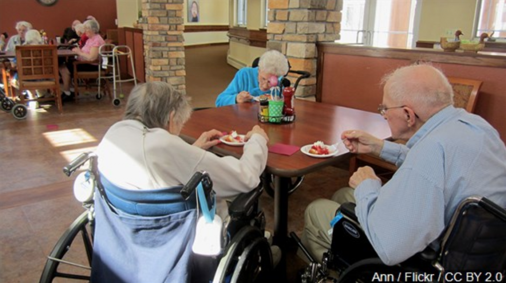 Three members of a nursing home sitting around a table eating
