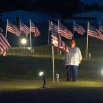 Field Of Honor Veterans Standing Next To Flags
