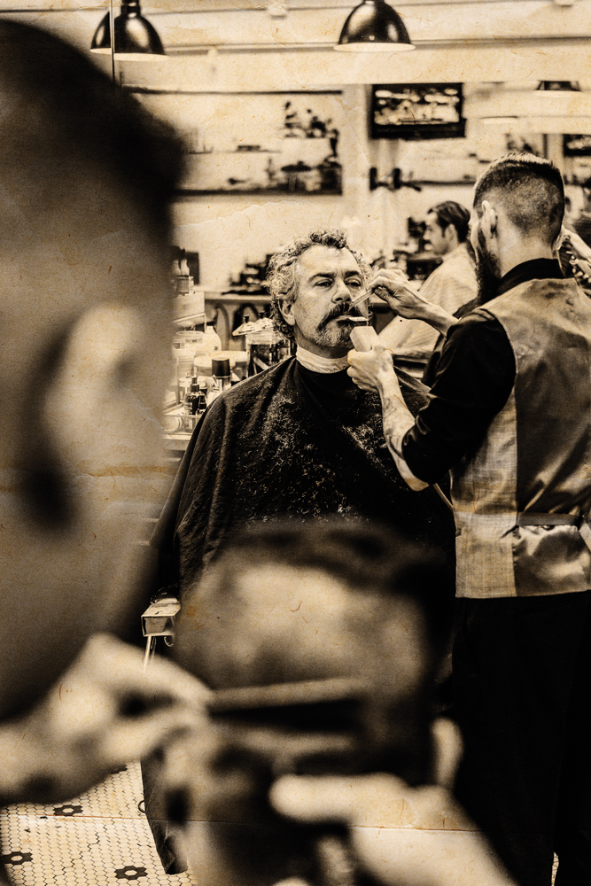 Markus Tran trims a customer's mustache at Mojo Barbershop and Social Club on Bethel Street in Chinatown. At Mojo, you will be offered a beer when you arrive. Photo: Aaron K. Yoshino