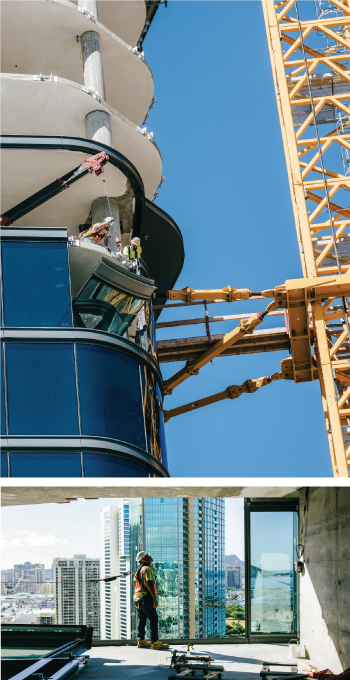 The windows are hoisted by crane to the floor above, then a small jib boom is used to lower them into place. Glaziers in safety harnesses guide the glass onto aluminum brackets embedded in the concrete.