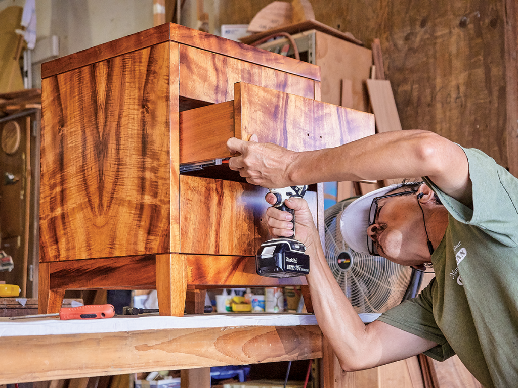 Master craftsman Bach Nguyen attaches the drawers to a curly koa, three drawer night stand. Photo by David Croxford