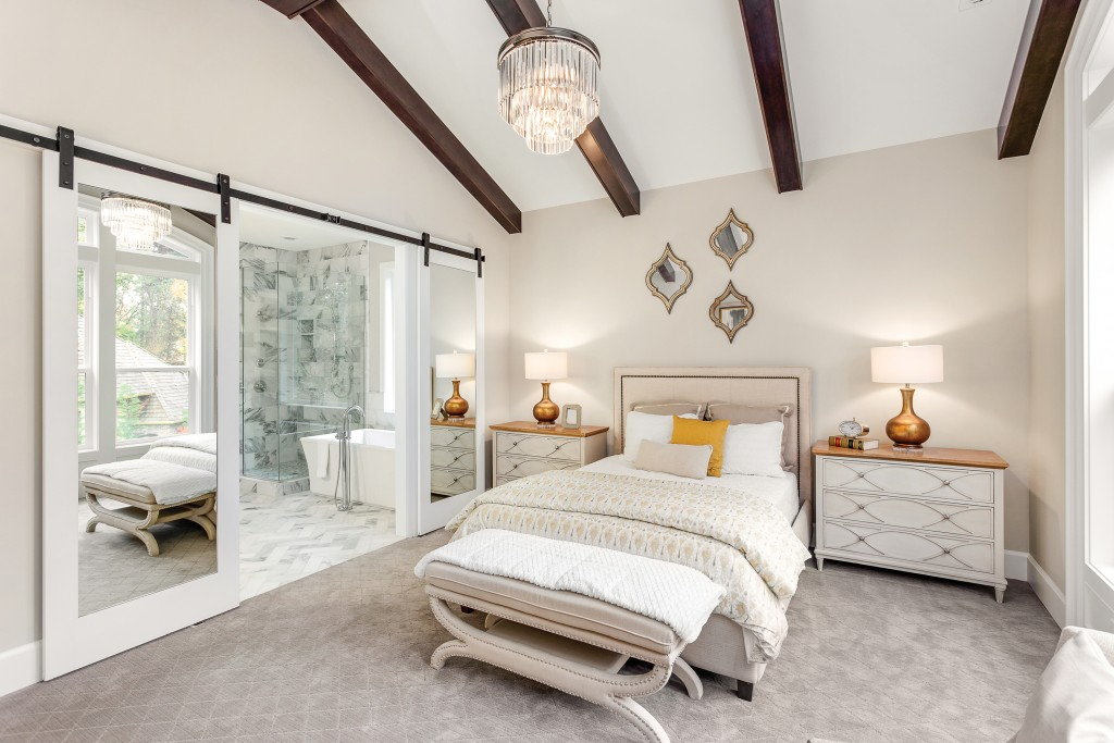 Master Bedroom In New Luxury Home With Chandelier And View Of Bathroom