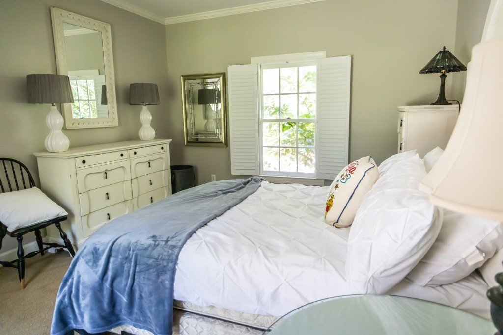 Guest Bedroom With White Bedding And A Blue Blanket