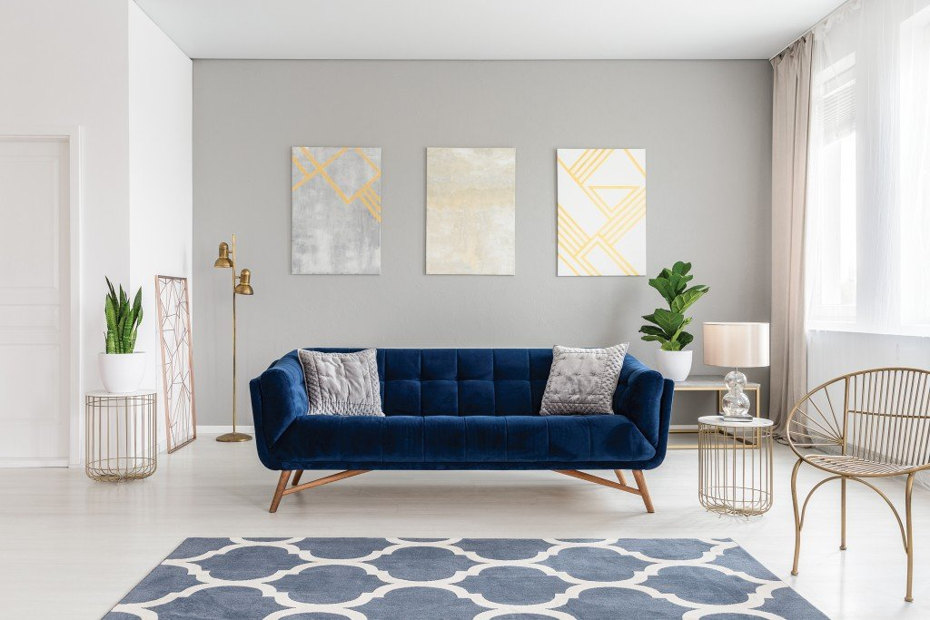 An Elegant Navy Blue Sofa In The Middle Of A Bright Living Room Interior