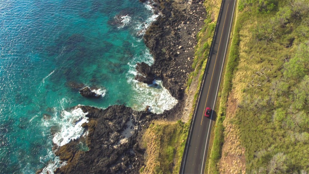 Aerial: Red Convertible Driving On Amazing Coastal Road Above Rocky Ocean Cliffs