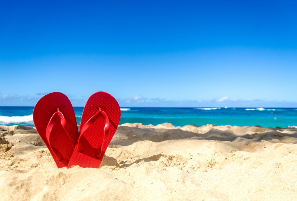 Red Flip Flops On The Sandy Beach