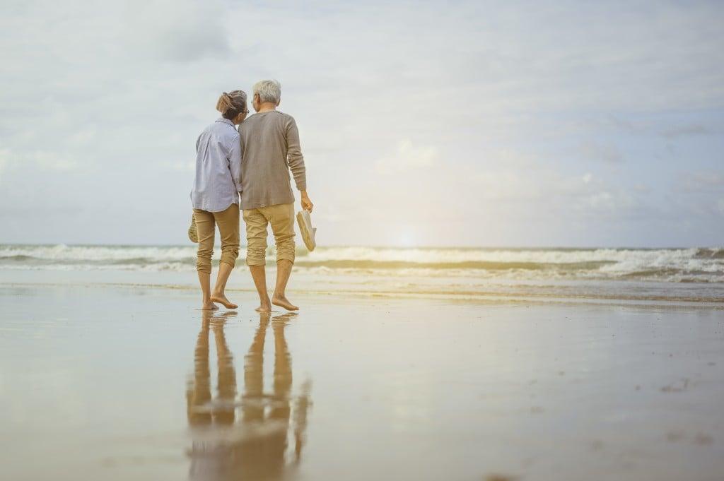 Senior Couple Walking On The Beach Holding Hands At Sunrise