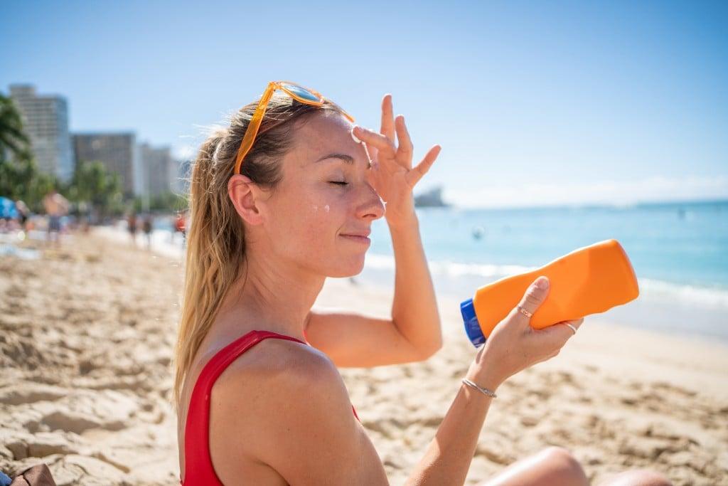 Woman On Beach Applying Sunscreen