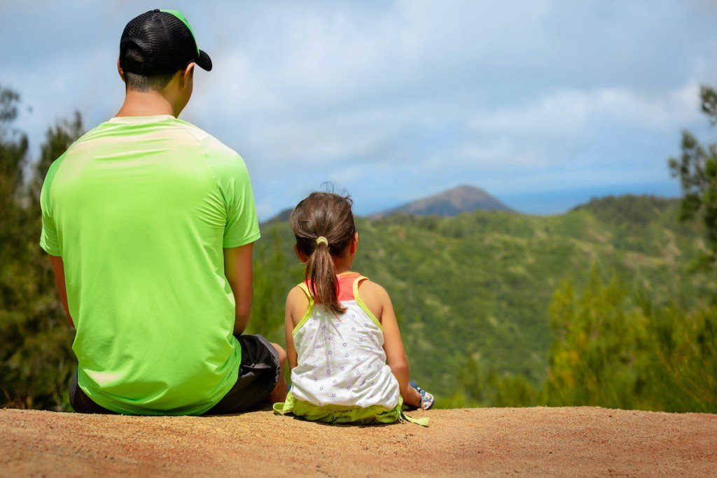 Father And Little Kid Sitting Together In Nature.