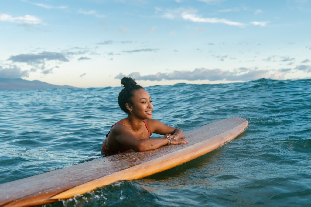 Young Woman Resting On Her Surfboard Waiting For A Wave
