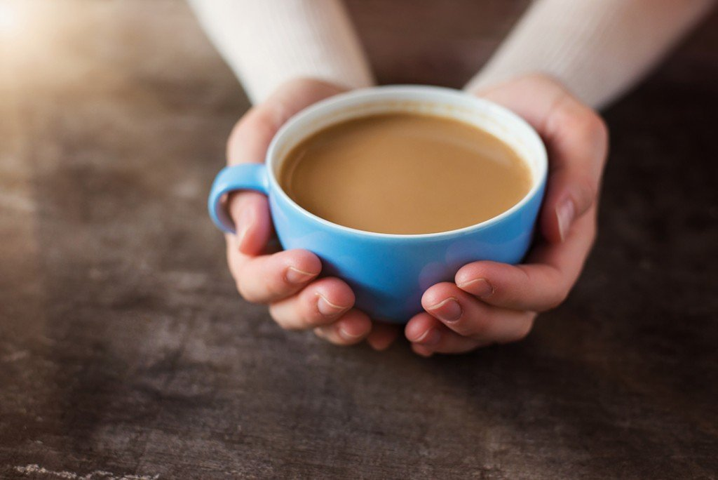 unrecognizable woman holding a cup of coffee