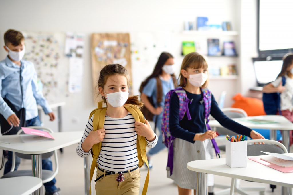 Group Of Children With Face Mask Back At School After Covid 19 Quarantine And Lockdown.