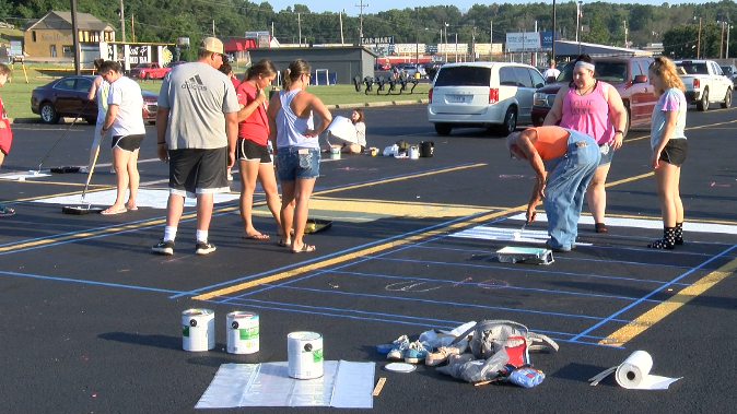 Neosho High School students paint their parking spaces to raise money for Project Graduation