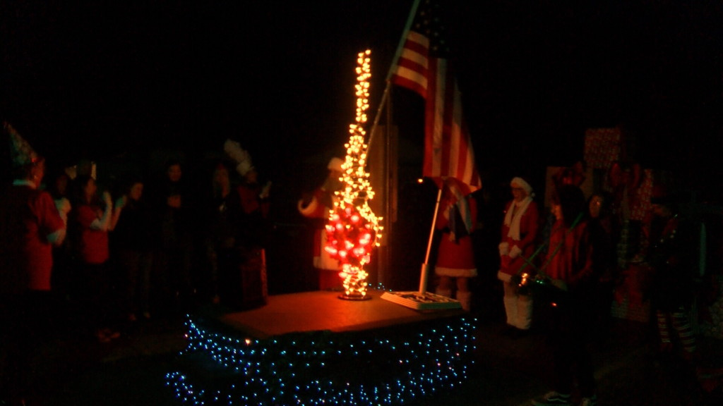Community comes together around historic water pump for parade, lighting ceremony