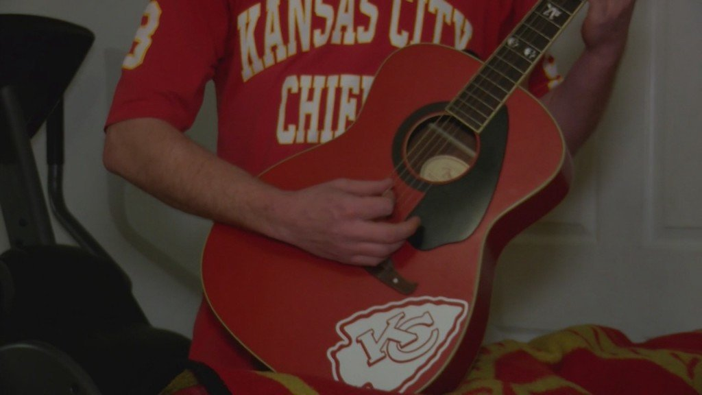 Rhatigan brother in Chiefs jersey playing guitar