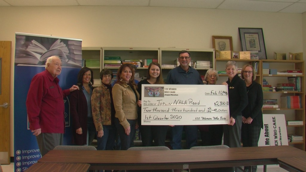 members of 100 women who care and nala with giant check