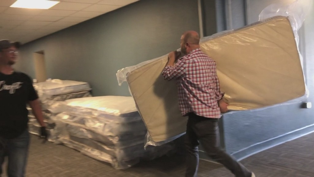 people carrying mattresses