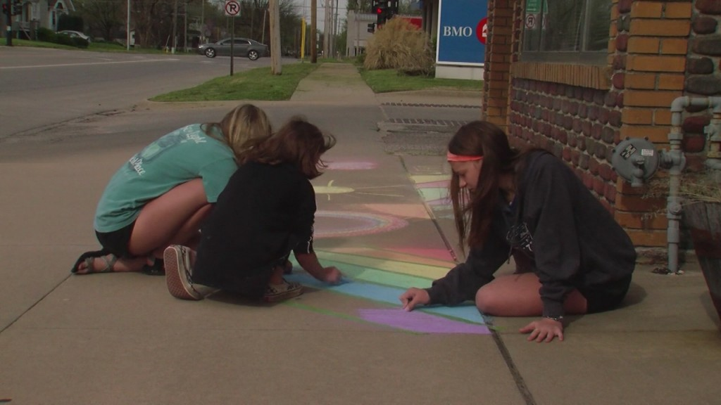 three girls drawing chalk art