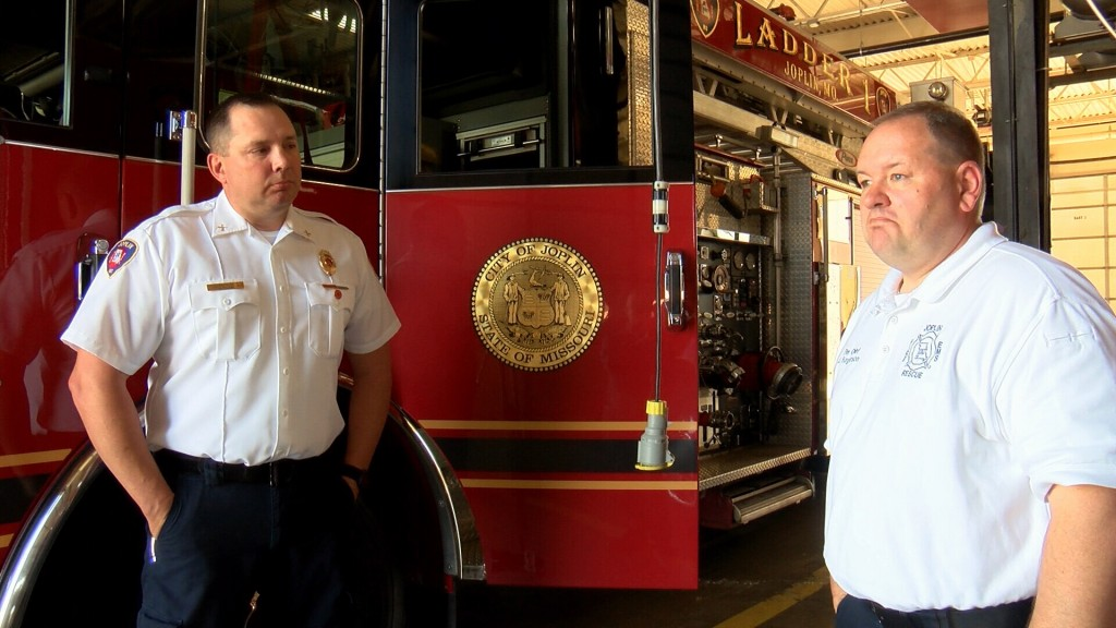 Joplin Firefighter John Miles talks with Chief Furgerson