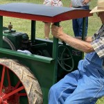 A Man Driving A Small Tractor