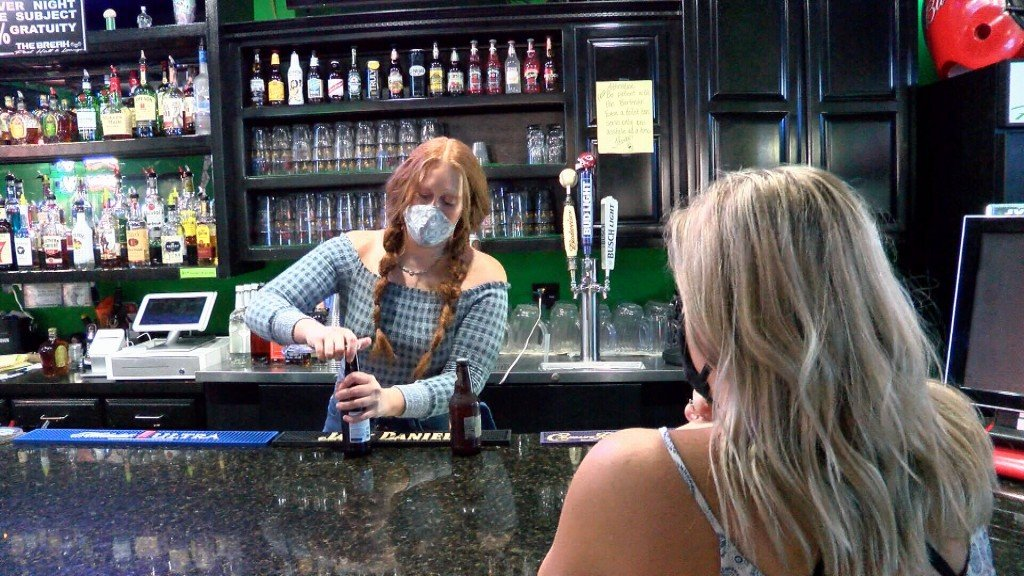 Bartender Opens Beer For Customer