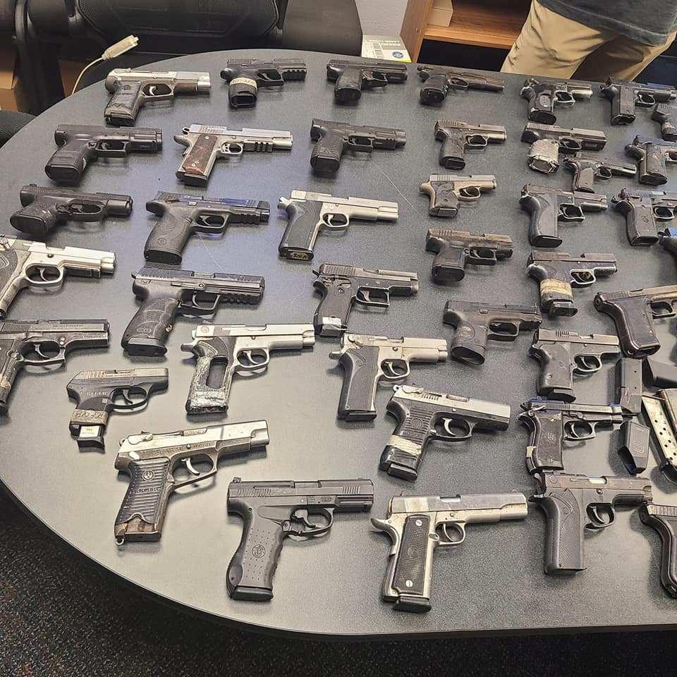 Miami police officers display stolen guns they recovered
