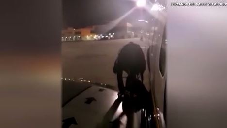 Disgruntled airline passenger opens emergency exit and hops on wing