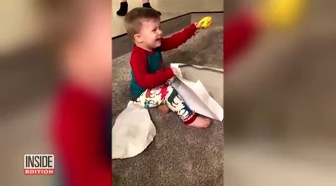 2-year-old boy in awe of banana he got for Christmas