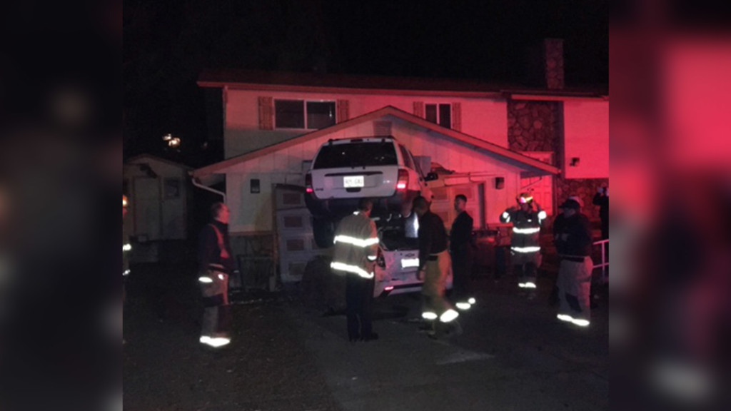 Police: Car stuck on top of another car, lodged into garage