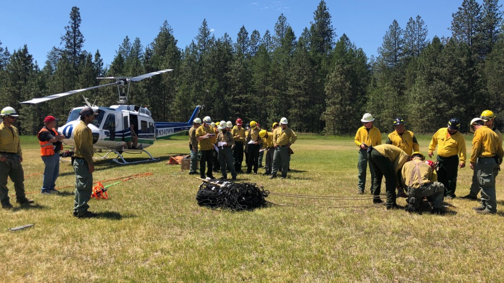 Firefighters work with helicopters at fire training academy