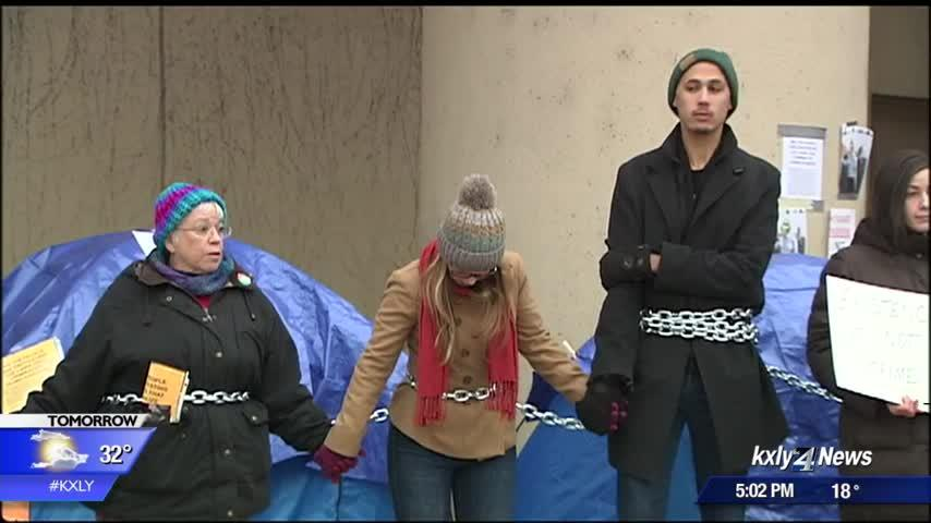 Protesters chain themselves together, continue protest over lack of warm shelters